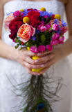 Wedding bouquet of pink, red, blue and yellow flowers and hand of bride Royalty Free Stock Photography