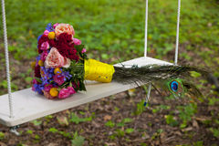 Wedding bouquet of pink, red, blue and yellow flowers and peacock feathers on swing Royalty Free Stock Photo