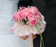 Wedding bouquet of pink roses. In hands of the bride and groom Stock Images