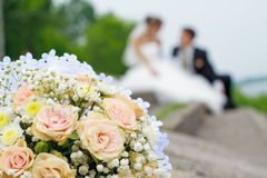 Wedding bouquet. With pink roses and fust merried couple on the background Stock Photo