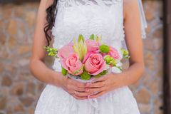 Wedding bouquet of pink roses and leaves. In the bride's hands Royalty Free Stock Photos