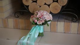 A wedding bouquet. Of pink roses tied with a ribbon of mint color lies by the fireplace stock video footage
