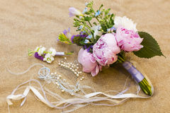 Wedding bouquet of pink, violet and blue flowers and ribbons, boutonniere and pearl barrette. On light brown blanket Stock Images