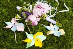 Wedding bouquet of pink, violet and blue flowers and three decorative paper windmills Royalty Free Stock Photography