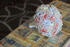 Wedding bouquet of pink, white, blue brooches. On old suitcase with drawings of old city Stock Images