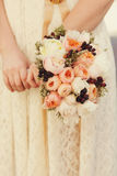 Wedding bouquet of pink and white ranunnculus is held by a bride Royalty Free Stock Photos