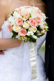 Wedding bouquet of pink and white roses in hand of bride. Wedding bouquet of pink and white roses and white and silver ribbons in hand of bride wearing white Stock Image