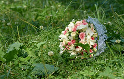 Wedding bouquet of pink and white roses lying on green grass Royalty Free Stock Photography