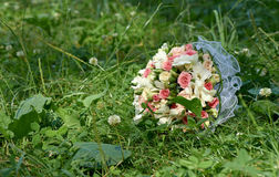 Wedding bouquet of pink and white roses lying on green grass. The Wedding bouquet of pink and white roses lying on green grass Royalty Free Stock Images