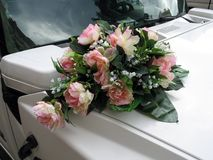 Wedding bouquet of pink and white roses. On the white limo hood Royalty Free Stock Photos
