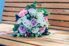 Wedding bouquet of purple and beige roses and snow-white lisianthus. Close-up royalty free stock image