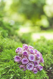 Wedding bouquet of purple roses lying on grass. Wqaiting for the wedding royalty free stock photo