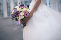 Wedding bouquet of purple and white flowers in the bride`s hands. A wedding bouquet of purple and white flowers in the hands of the bride. Horizontal photo Royalty Free Stock Photo