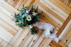 Wedding bouquet of purple and white flowers tied. With ribbons on the parquet Royalty Free Stock Photos