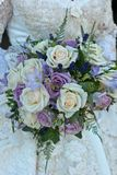 Wedding Bouquet  of purple and white roses. Bride holding a wedding Bouquet  of purple and white roses Stock Photo
