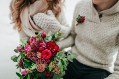 Wedding bouquet with red and crimson flowers on blurred bride and groom background. Winter wedding outdoors Royalty Free Stock Image