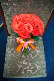 Wedding bouquet with red flowers on a chair with a ring Stock Photography