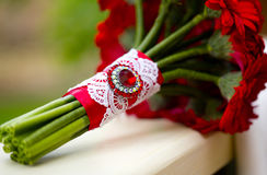 Wedding bouquet of red gerbera with red brooch and lace. Wedding bouquet of red gerbera or chamomile or daisy with red or crimson brooch and white lace on window Royalty Free Stock Images