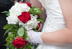 Wedding bouquet of red roses and white flowers. Holding by a bride Royalty Free Stock Photography