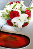 Wedding bouquet of red roses and white lilies. Lying on the car Royalty Free Stock Images