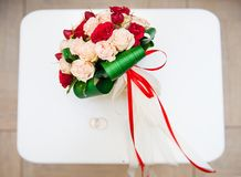 Wedding bouquet with red and white flowers on a chair with a ring.  Royalty Free Stock Images