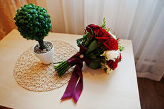 Wedding bouquet of red and white rose and ribbon on table Royalty Free Stock Photo