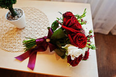 Wedding bouquet of red and white rose and ribbon on table Stock Photography