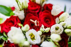 Wedding bouquet of red and white roses and gold wedding rings. stock photos