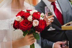 Wedding bouquet of red and white roses in the hand of the bride and a glass of champagne in the other hand royalty free stock image