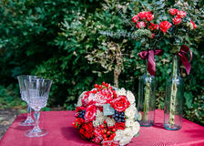 A wedding bouquet of red and white roses and red. And blue berries on a burgundy tablecloth next to two glasses and two bottles of flowers. Wedding floral Stock Image