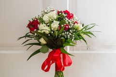 Wedding bouquet of red and white roses, tied with a red ribbon, on the background of white doors.  Royalty Free Stock Photo