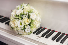 Wedding bouquet and ring lying on white piano Stock Image