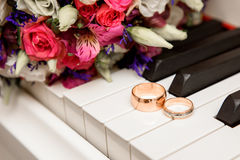 Wedding bouquet and ring lying on white piano Stock Photos