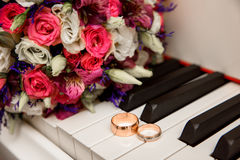Wedding bouquet and ring lying on white piano Royalty Free Stock Photo