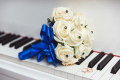 Wedding bouquet and ring lying on white piano. A bouquet and a ring lying on a white piano. Beautiful vintage wedding background Stock Photos