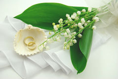 Wedding bouquet and rings. Lily of the valley wedding bouquet, two wedding rings and a seashell Stock Photos