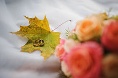 Wedding bouquet and rings. Background wedding dress in yellow autumn leaves Royalty Free Stock Photos