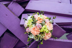 Wedding bouquet with rings. Beautiful weding bouquet with rings on purple wooden background stock photography