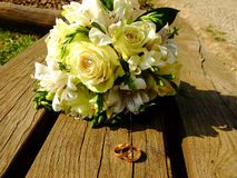 Wedding Bouquet and Rings. Beautiful white wedding Bouquet and two golden Rings on the Bench Royalty Free Stock Photo