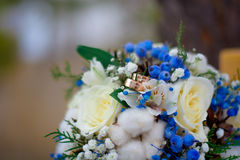 Wedding bouquet and rings. Blue wedding bouquet of white roses with wedding rings Stock Images