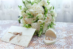 Wedding bouquet, rings and card on lace cloth Stock Photography