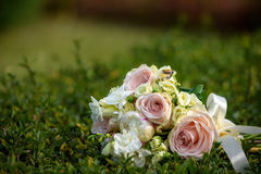 Wedding bouquet with rings on grass. Stock Images
