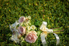 Wedding bouquet with rings on grass. Stock Image