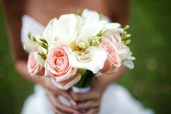 Wedding bouquet with rings on it in the hands of the bride stock photos