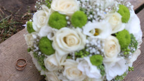 Wedding bouquet and rings on a wooden board Royalty Free Stock Photography