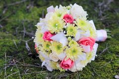 Wedding bouquet of rose, chrysanthemum , iris, and gypsophila on the forest moss.  Stock Photography