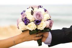 Wedding bouquet with roses. Colorful wedding bouquet with roses holded by newlyweds bride and groom Royalty Free Stock Photography