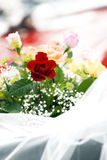 Wedding Bouquet Of Roses. Closeup detail of wedding flowers with roses with greenery and baby's breath. Veil is draped across in front of the bouquet Royalty Free Stock Photo