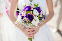 Wedding bouquet with roses and alstromeria. Colorful wedding bouquet in bride's hands with eustomas and alstromeria Royalty Free Stock Photo