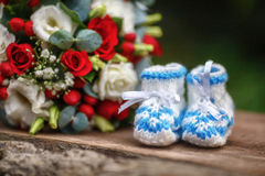 Wedding bouquet of roses and baby booties on wooden background Stock Photography